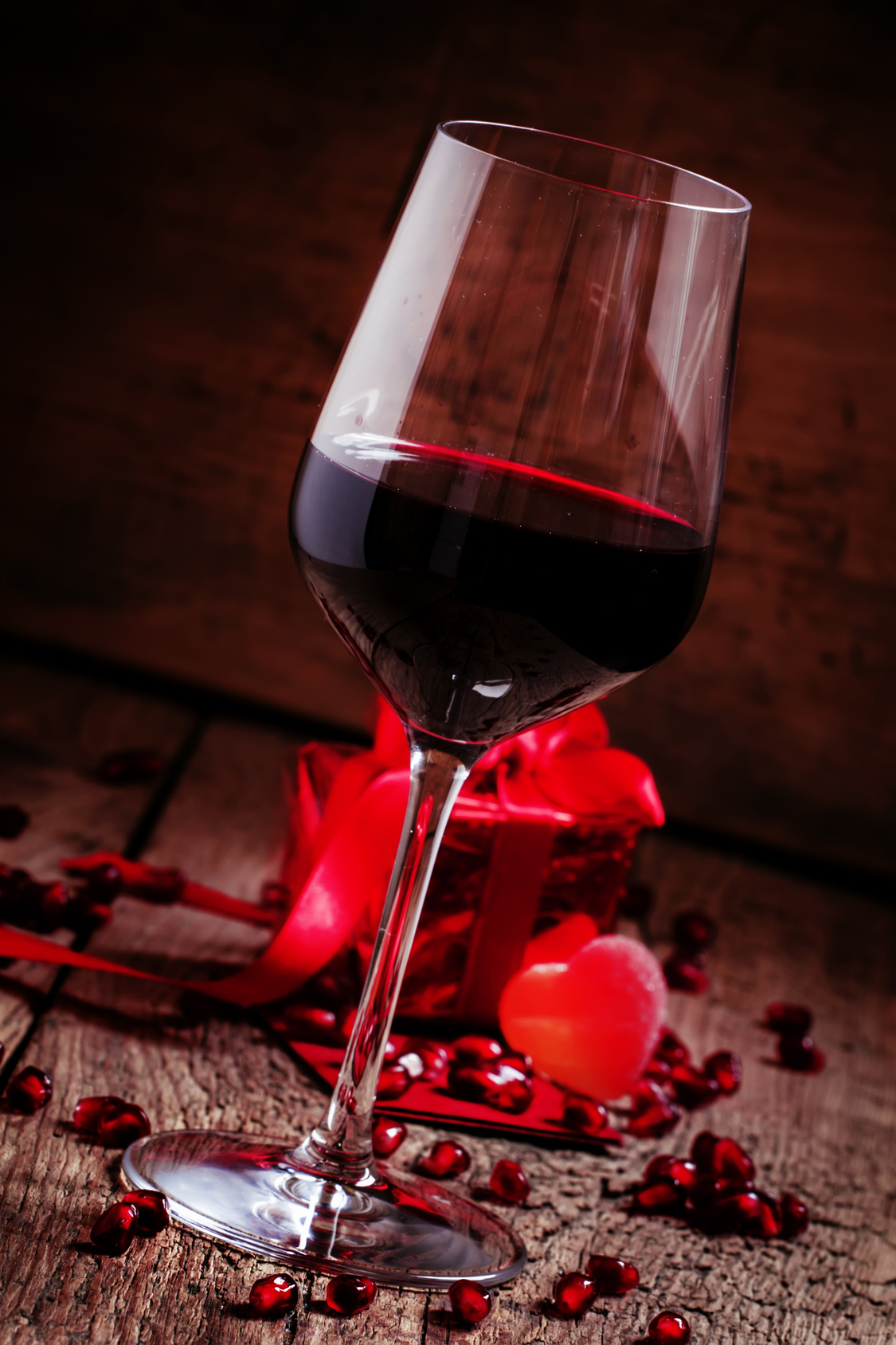 Red wine in a glass, a gift in the red packing on the old wooden background, selective focus
